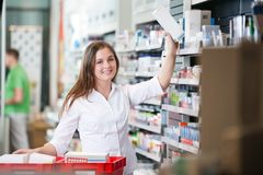 Female Keeping a Box on Shelf Stock Image