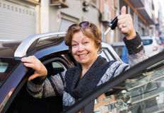 Female with keys near car. Portrait of happy mature female with keys near car Royalty Free Stock Images