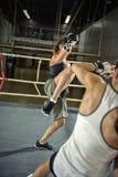 Female kick boxer practicing attack Stock Photos