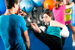 Female kick boxer with trainer in sparring Royalty Free Stock Images
