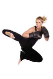 Female kickboxer in the air. A female kickboxer performing a flying side kick in the air isolated on a white background Royalty Free Stock Photos