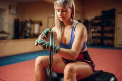 Female kickboxer sitting on punching bag in gym royalty free stock photos