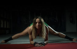 Female kickboxer doing splits and lunges Royalty Free Stock Photo