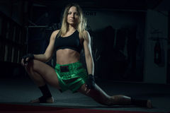 Female kickboxer doing splits and lunges Stock Photo