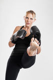 Female kickboxer kicking portrait Royalty Free Stock Photo