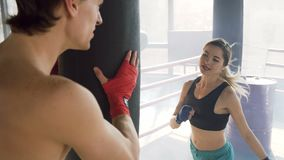 Female kickboxer training with coach in boxing club. stock video footage