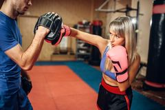 Female kickboxer on workout with personal trainer royalty free stock image