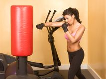 Female kickboxing exercise. Attractive woman kickboxing using red punching bag Royalty Free Stock Photography