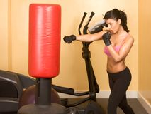 Female kickboxing training. Attractive woman kickboxing with red punching bag Stock Image