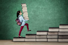 Female kid carrying textbooks Royalty Free Stock Image