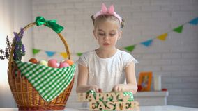 Female kid counting colored eggs and putting in basket, happy Easter greeting stock footage