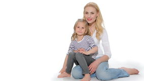 Female kid and her mom show their thumbs. Pretty little girl with her mom showing their thumbs up. Attractive caucasian woman with her kid okaying to the camera stock video footage