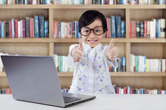 Female kid with laptop shows hands gesture Stock Photo