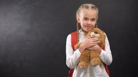 Female kid with rucksack hugging teddy bear smiling on camera against blackboard stock video footage