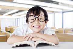 Female kid smiling at the camera while reading book Stock Photography