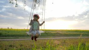 Female kid swaying, happy little child have fun sway spin on swing, nature sunset, forest park, children on swing stock video footage