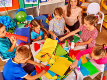 Female kid work with colored paper in beginner school. Royalty Free Stock Image