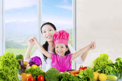 Female kids and mother with vegetables Stock Photos