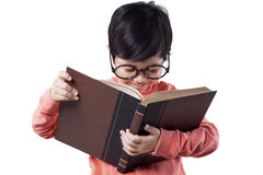 Female kindergarten student reads literature Royalty Free Stock Image