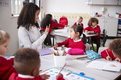 Female kindergarten teacher sitting at table in a classroom talking and gesturing to a young Chinese schoolgirl, selective focus royalty free stock photography