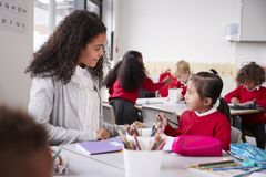Female kindergarten teacher sitting at table in a classroom talking to a young Chinese schoolgirl, close up royalty free stock images