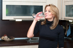 Female in kitchen drinking champagne Royalty Free Stock Image