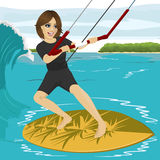 Female kiteboarder enjoys surfing waves with kiteboard Royalty Free Stock Photos