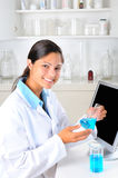 Female Lab Technician. Young female Lab Tech holding up a flask of blue chemicals in laboratory setting. Vertical format Royalty Free Stock Photo