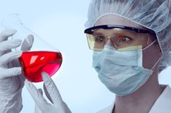 Female lab technician and flask with red liquid Stock Photography