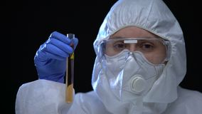 Female lab worker examining test tube with detergent, chemistry, caution sign. Stock footage stock video