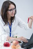Female Laboratory Assistant With Different Test Flasks Conducting Experiment in laboratory With Fruit Stock Photos