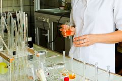 A female laboratory assistant, a doctor, a chemist, works with flasks, test tubes, makes solutions, medicines, mixes ingredients stock image