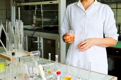 A female laboratory assistant, a doctor, a chemist, works with flasks, test tubes, makes solutions, medicines, mixes ingredients. A female laboratory assistant stock photography