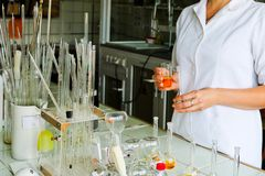 A female laboratory assistant, a doctor, a chemist, works with flasks, test tubes, makes solutions, medicines, mixes ingredients stock images