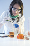 Female Laboratory Staff Dealing with Flasks Filled with Chemicals Specimens During Scientific Experiment Stock Photography