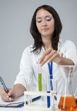Female Laboratory Staff Working With Flasks Filled with Liquids Stock Photography