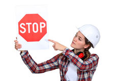 Female laborer pointing stop sign Stock Photo