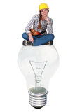 Laborer sitting on light bulb Royalty Free Stock Photo
