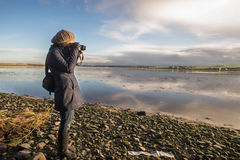 Female landscape photographer. Female photographer shooting water reflection at sunset Royalty Free Stock Images