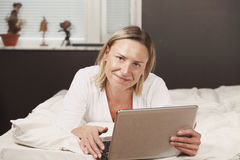 Female with laptop on bed Royalty Free Stock Photo