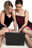 Female laptop users. Two women sat on the floor looking at a laptop computer Royalty Free Stock Photo