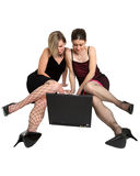 Female laptop users. Two women sat on the floor looking at a laptop computer Royalty Free Stock Images
