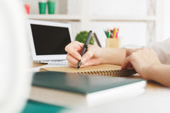 Female with laptop writing in notepad. Close up of female hands writing in spiral notepad placed on wooden desktop with blank laptop screen. Paperwork concept royalty free stock photos