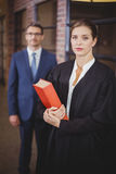 Female lawyer with businessman standing in background Stock Image