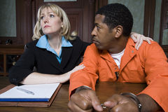 Female Lawyer With Criminal In Courtroom Stock Photos