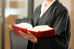 Female lawyer with German civil code. Female lawyer with German civil law code in a court room royalty free stock photo