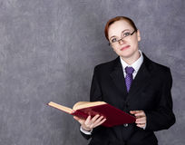Female lawyer holding a big book with serious expression, woman in a man`s suit, tie and glasses.  Royalty Free Stock Image