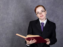 Female lawyer holding a big book with serious expression, woman in a man`s suit, tie and glasses.  Stock Images