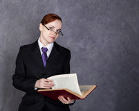 Female lawyer holding a big book with serious expression, woman in a man`s suit, tie and glasses.  Stock Image