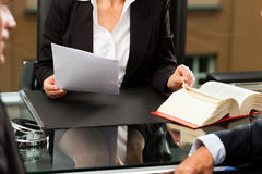 Female Lawyer or notary in her office. Mature female lawyer or notary with client in her office for counseling stock images